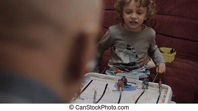 Boy playing table hockey with grandpa