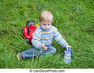 boy playing toy truck in grass