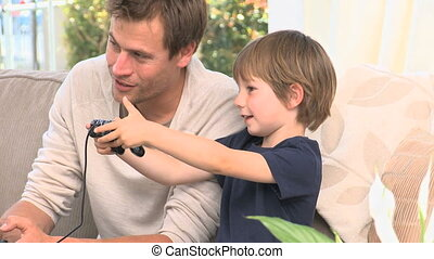 Boy playing video gemes with his father