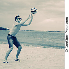 Boy playing volleyball on the beach