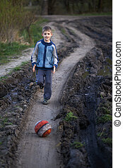 boy playing with a ball on the mud road
