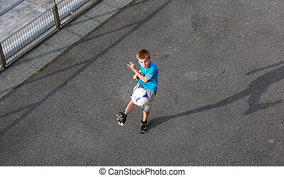 Boy playing with a ball on the street