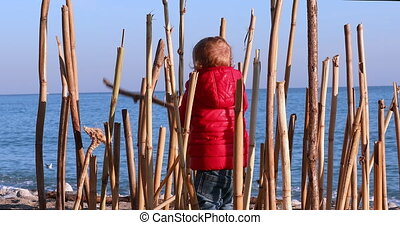 Boy Playing With A Bamboo Stick On Beach Alone