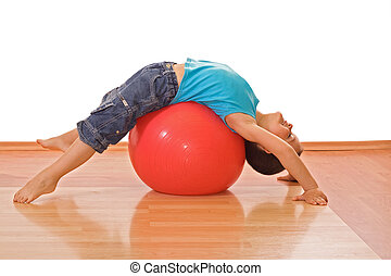 Happy little boy stretching on a gymnastic ball - isolated