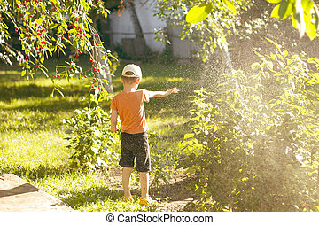 Boy playing with a sprinkler in the garden