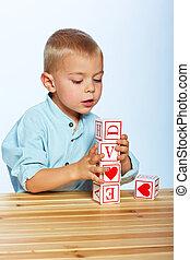 boy playing with alphabet blocks