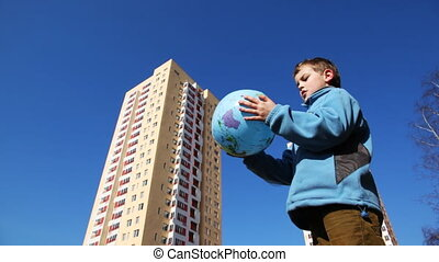 boy playing with ball in form of Planet Earth