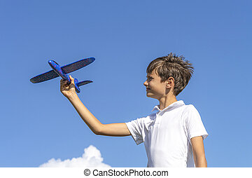 Boy playing with blue toy plane against blue sky