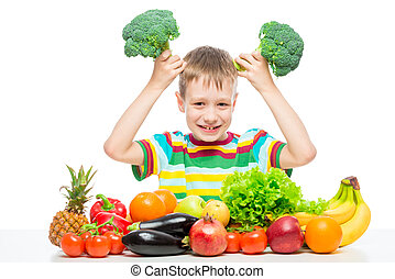 Boy playing with broccoli at the table with a bunch of vegetables and fruits in the studio