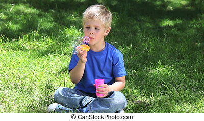 Boy playing with bubbles in a park