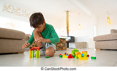 Boy playing with building blocks on floor in living room at comfortable home