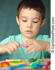 Boy playing with color play dough