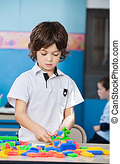 Boy Playing With Colorful Blocks In Classroom