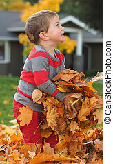 Boy playing with fall leaves