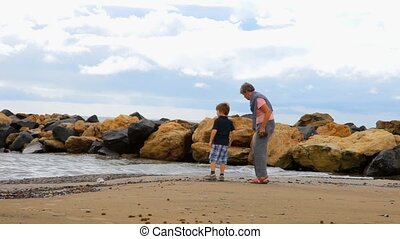 Boy playing with grandma on beach