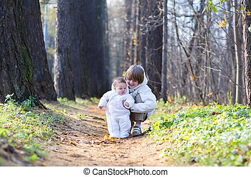 Boy playing with his baby sister in the park on a cold day
