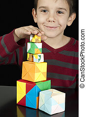 Boy playing with multicolored cubes