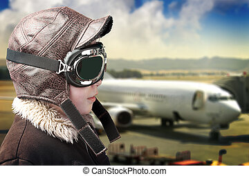 Boy dressed up in pilot`s outfit, jacket, hat and glasses.