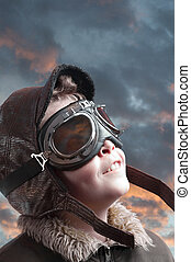 Boy playing with pilot?s hat and cloudy background