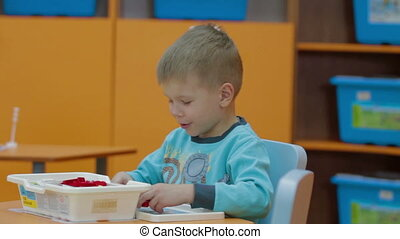 Boy playing with plastic building blocks at kindergarten