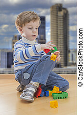 Boy playing with plastic construction with contemporary buildings in background