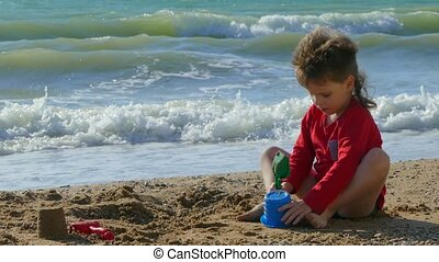 Boy playing with sand on the beach by the sea - A child is a...