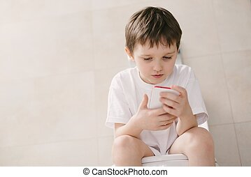 Boy playing with smartphone while sitting on toilet.