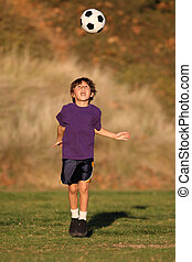 Boy playing with soccer ball in Fall