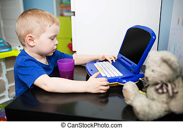 Boy playing with toy computer