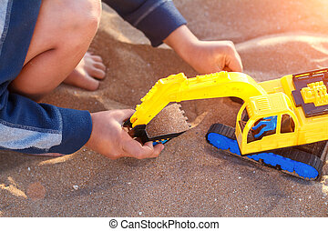 boy playing with toy in the sand