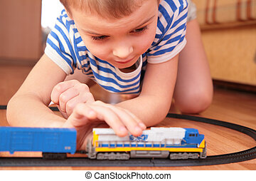 Boy playing with toy railroad