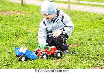 Boy playing with toy tractor