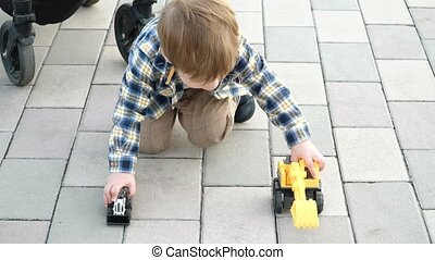 Boy playing with toy tractors in city park