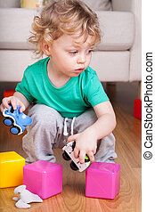 Boy playing with toys on the floor
