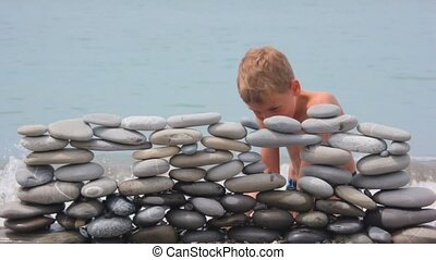 boy playing with wall of stones on beach, sea surf in background