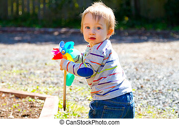 Boy Playing With Wind Toy - A one year old boy plays with a...