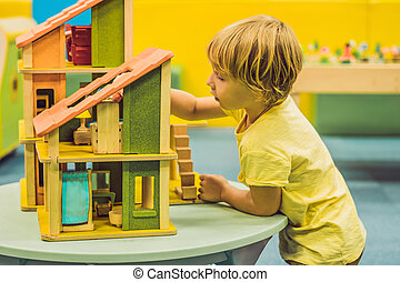 Boy playing with wooden house in kindergarten