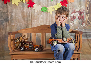 Boy playing with wooden toy cars.