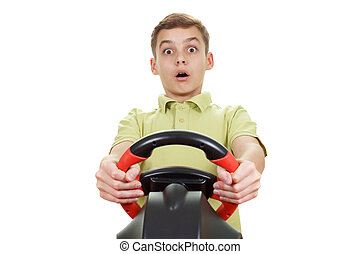 Boy plays a driving game console, isolated on white