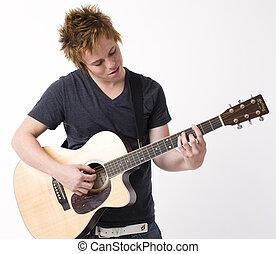 A boy plays acoustic guitar