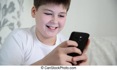 boy plays on the smartphone and laughing