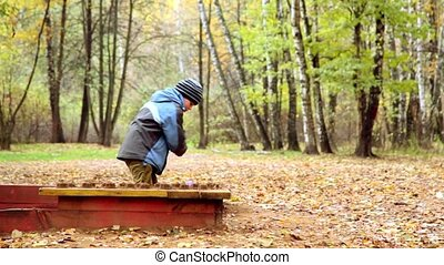 Boy plays sand on playground in park