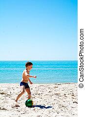 boy plays soccer on beach