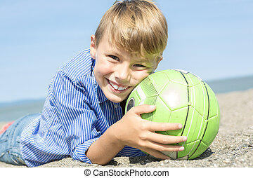 boy plays soccer on the beach