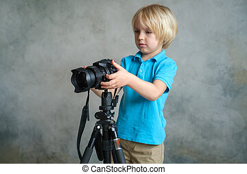 Boy plays with a professional photo camera