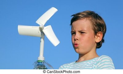 boy plays with a wind-driven generator against sky - boy...