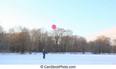 boy plays with air-balloon in snowfield