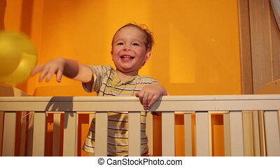 Boy plays with balloon in the playpen.