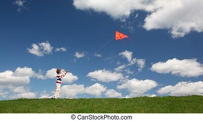 Boy plays with kite in meadow - boy plays with orange kite...