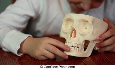 Boy plays with skull